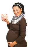 Happy pregnant woman with piggy bank Royalty Free Stock Image