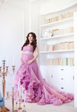 Happy pregnant woman in pink dress stands near shelves of books and candles . Fashion shot Stock Photo