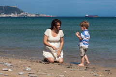Happy pregnant woman playing with child boy on the beach Royalty Free Stock Photography