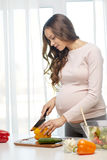 Happy pregnant woman preparing food at home Royalty Free Stock Photography
