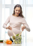 Happy pregnant woman preparing food at home Royalty Free Stock Images