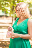 Happy pregnant woman pulls out a pink baby booties from a packag Royalty Free Stock Image