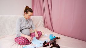 Happy pregnant woman puts baby clothes in maternity hospital  in last month of pregnancy stock video footage