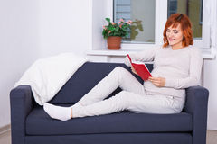 Happy pregnant woman reading book in living room Royalty Free Stock Photography