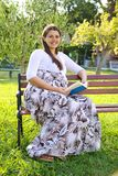 Happy pregnant woman reading book in nice garden Royalty Free Stock Images
