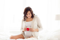 Happy pregnant woman with red heart in bed at home Stock Photos