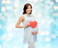 Happy pregnant woman with red heart touching belly Stock Photos