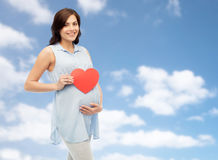 Happy pregnant woman with red heart touching belly Royalty Free Stock Photography