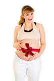 Happy pregnant woman with red ribbon on belly Royalty Free Stock Photography