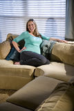 Happy pregnant woman relaxing on sofa Stock Photography