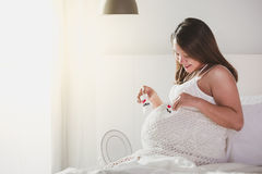 Happy pregnant woman is resting at home on the bed and holding a Stock Images