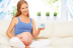 Happy pregnant woman is resting at home on sofa and holding a bl. Happy pregnant woman is resting at home on the sofa and holding a little blue booties socks Stock Photos