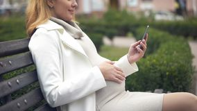 Happy pregnant woman scrolling smartphone photos, relaxing in park on bench stock photos