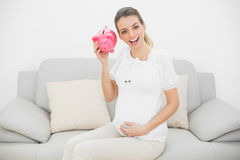 Happy pregnant woman shaking a pink piggy bank Royalty Free Stock Photo