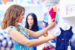 Happy pregnant woman shopping in baby store royalty free stock photo