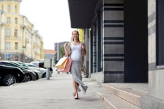 Happy pregnant woman with shopping bags at city Stock Photos