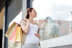 Happy pregnant woman with shopping bags at city. Pregnancy, motherhood, people and expectation concept - happy smiling pregnant woman with shopping bags at city Stock Photography