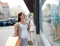 Happy pregnant woman with shopping bags at city. Pregnancy, motherhood, people and expectation concept - happy smiling pregnant woman with shopping bags at city Stock Images