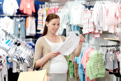 Happy pregnant woman shopping at clothing store. Pregnancy, people, sale and expectation concept - happy pregnant woman with shopping bag buying baby bodysuit at Stock Photography
