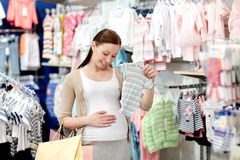 Happy pregnant woman shopping at clothing store. Pregnancy, people, sale and expectation concept - happy pregnant woman with shopping bag buying baby bodysuit at Stock Photo