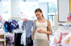 Happy pregnant woman shopping at clothing store. Pregnancy, people, sale and expectation concept - happy pregnant woman shopping and buying baby bodysuit at Stock Photo