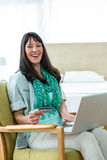 Happy pregnant woman shopping online on her laptop Royalty Free Stock Photos
