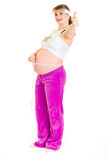 Happy pregnant woman showing thumbs up gesture Stock Photo