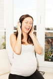 Happy pregnant woman singing Royalty Free Stock Images