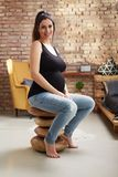 Happy pregnant woman sitting at home Stock Images