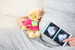 Happy pregnant woman sitting on sofa at home hand holding bear d. Oll and showing ultrasound scan photo on belly. Pregnancy, Fetal examination, Antenatal Care Stock Photography