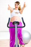 Happy pregnant woman sitting on static bicycle Royalty Free Stock Photo