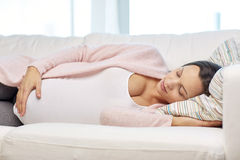 Happy pregnant woman sleeping on sofa at home Stock Photography