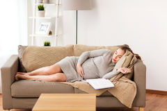 Happy pregnant woman sleeping on sofa at home Stock Images