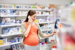 Happy pregnant woman with smartphone at pharmacy Royalty Free Stock Photos