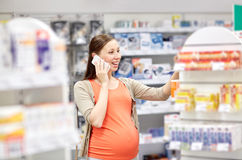 Happy pregnant woman with smartphone at pharmacy Royalty Free Stock Photo