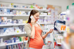 Happy pregnant woman with smartphone at pharmacy Stock Photo