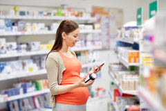 Happy pregnant woman with smartphone at pharmacy Stock Images