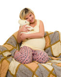Happy pregnant woman on sofa Stock Photo