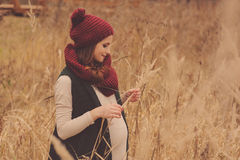 Happy pregnant woman in soft warm cozy outfit walking outdoors Royalty Free Stock Photo