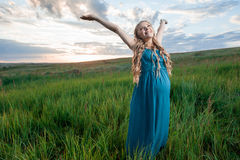 Happy pregnant woman stand on meadow Stock Image