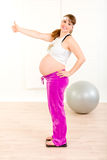 Happy pregnant woman standing on weight scale Royalty Free Stock Photo