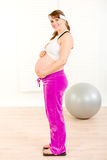 Happy pregnant woman standing on weight scale. And holding her belly royalty free stock image