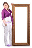 Happy pregnant woman stands near large frame Stock Image