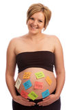 Happy pregnant woman with sticky notes on belly Royalty Free Stock Photography
