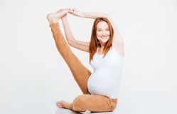 Happy pregnant woman stretching leg on the floor Stock Images