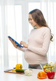 Happy pregnant woman with tablet pc cooking food Stock Photos