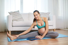 Happy pregnant woman with tablet pc exercising Stock Images