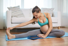 Happy pregnant woman with tablet pc exercising Stock Photos