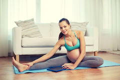 Happy pregnant woman with tablet pc exercising Royalty Free Stock Photo