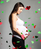 Happy pregnant woman touching her belly Stock Photos